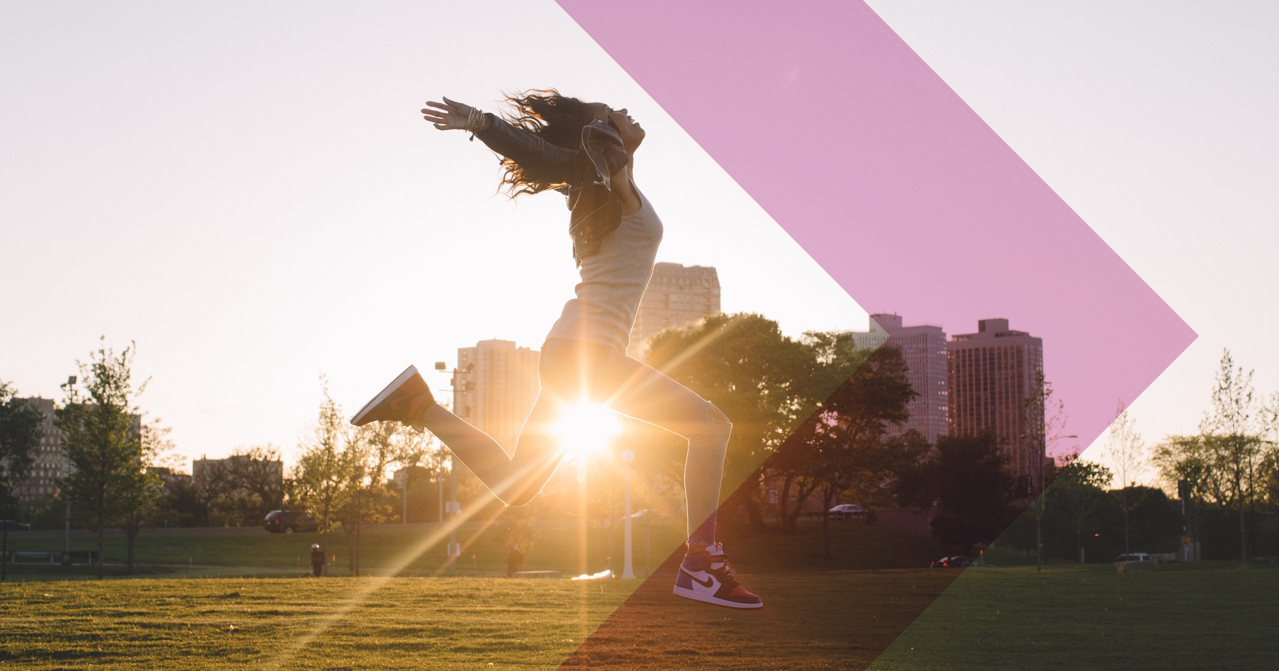 A woman jumps for joy in a field with the sun behind her