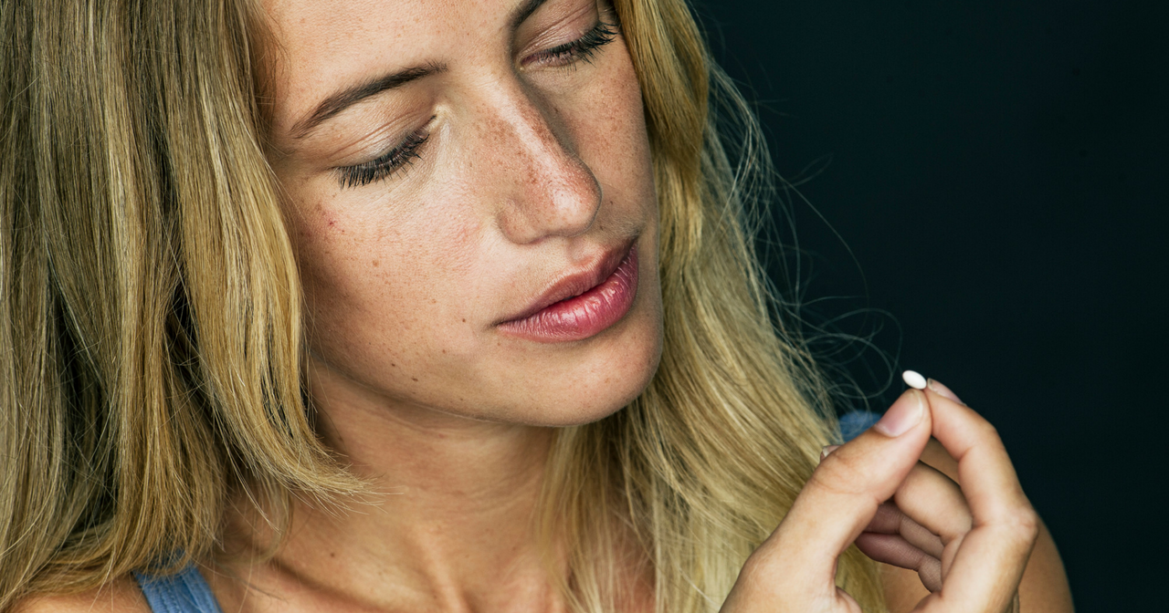 A woman considers a pill she's holding in her hand.
