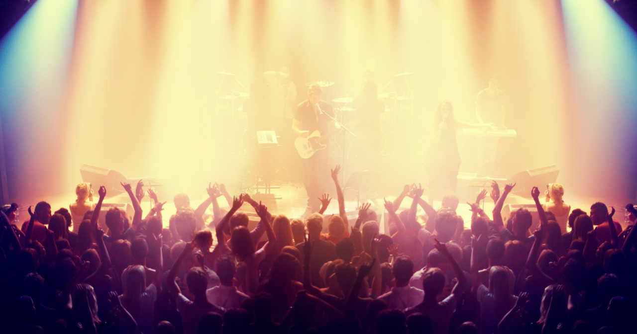 An image of a concert and the audience with their hands up