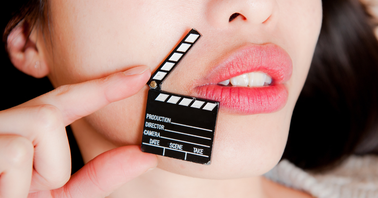 A black and white movie clapper next to a woman's lips