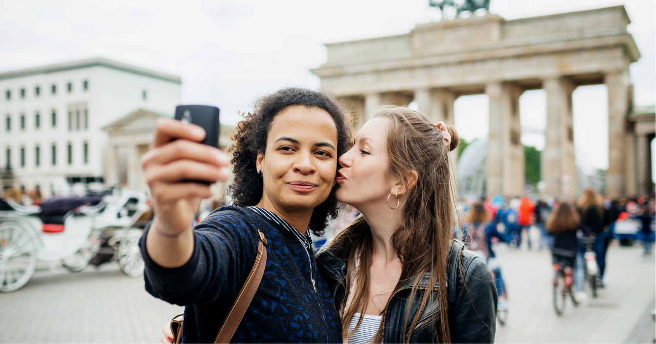 A woman kisses her girlfriend's cheek as they take a selfie