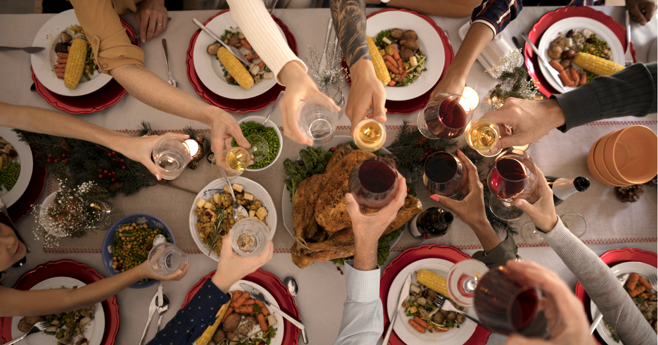 A group of hands toast with glasses over a holiday table