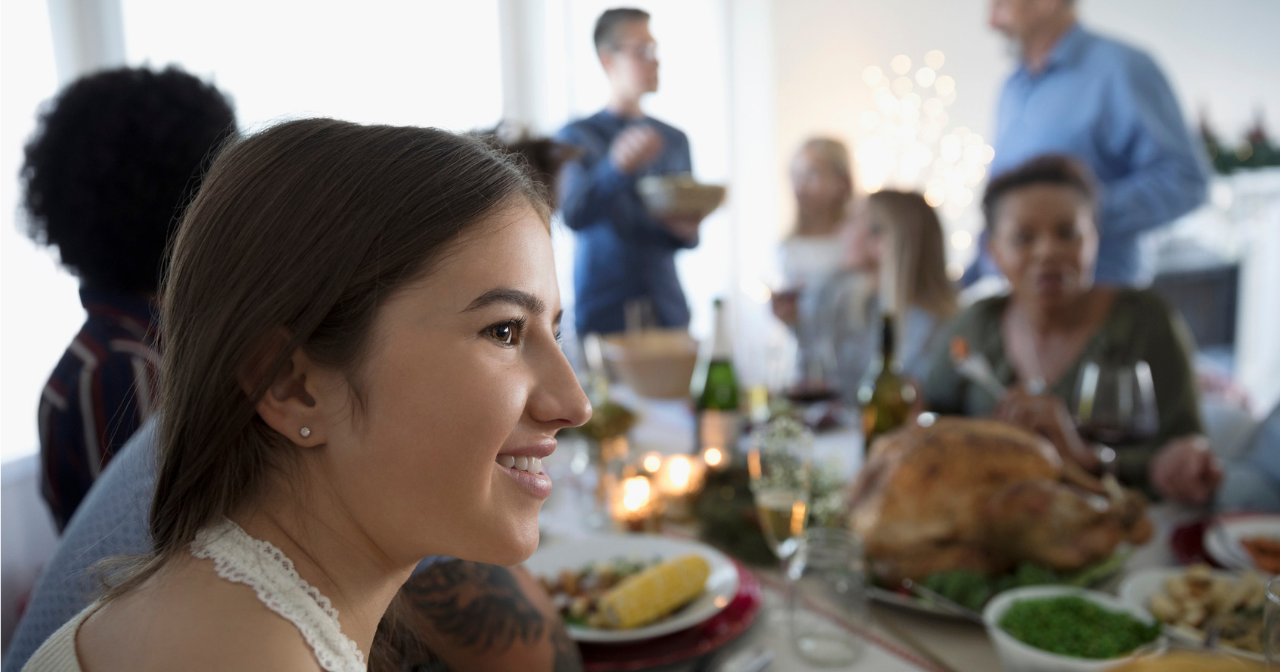 a young woman sits at a holiday table with a smile