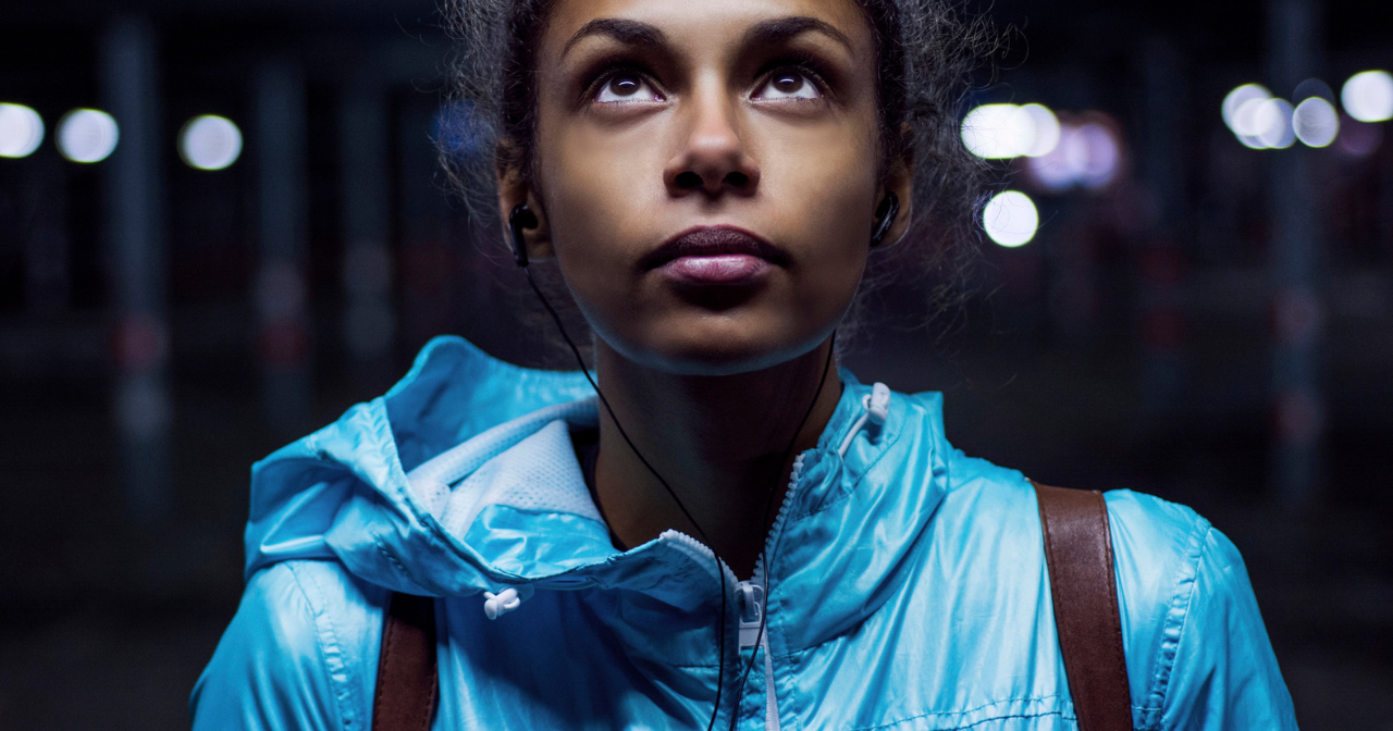 A young black woman in a bright jacket looks up