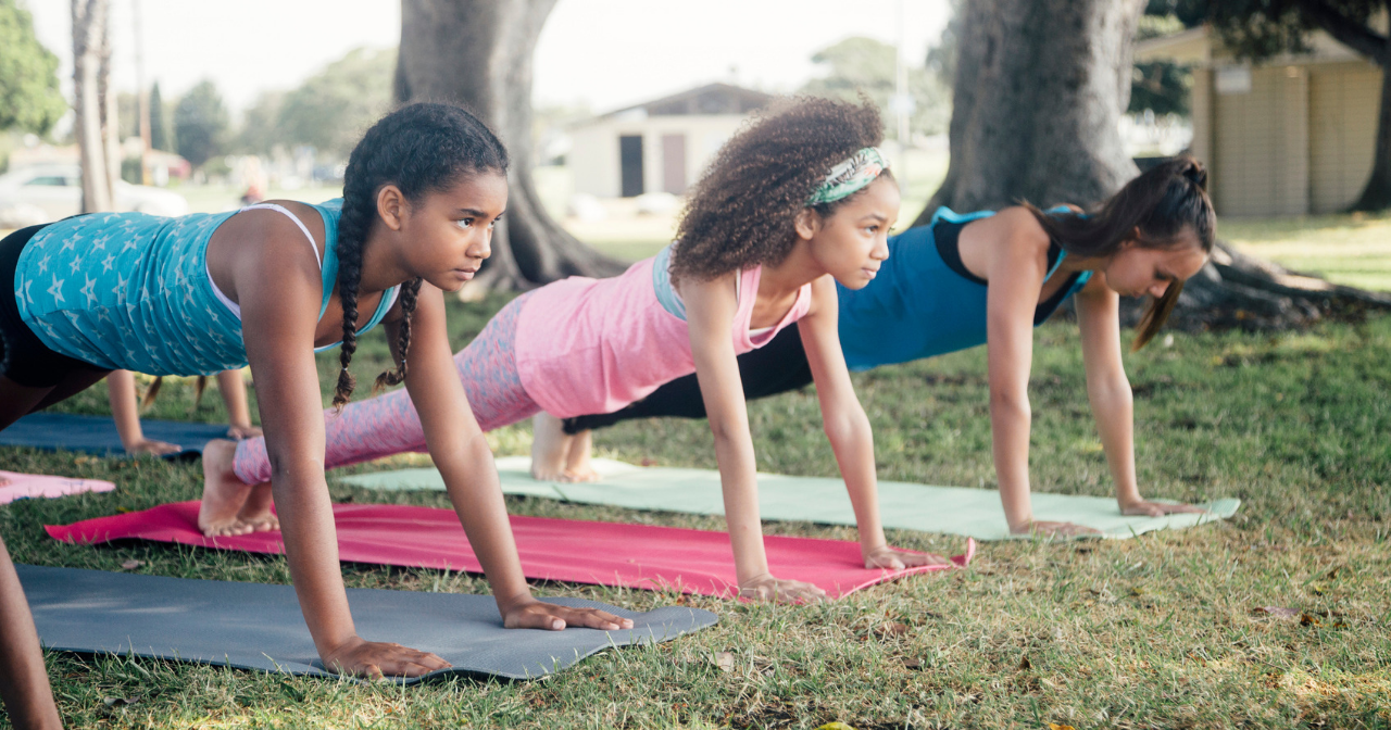Three young girls do yoga outdoors