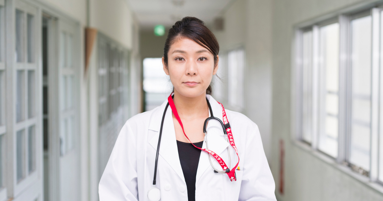 An Asian American doctor looks straight into the camera