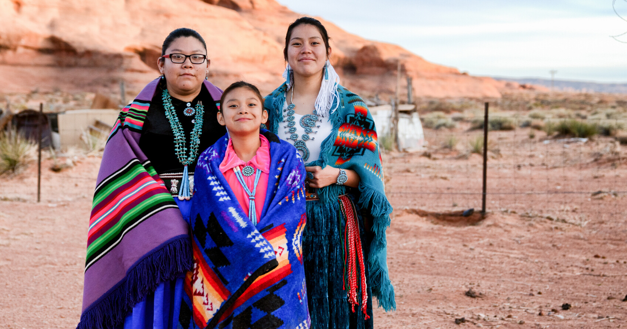 Three young Native women smile while wearing traditional clothes.