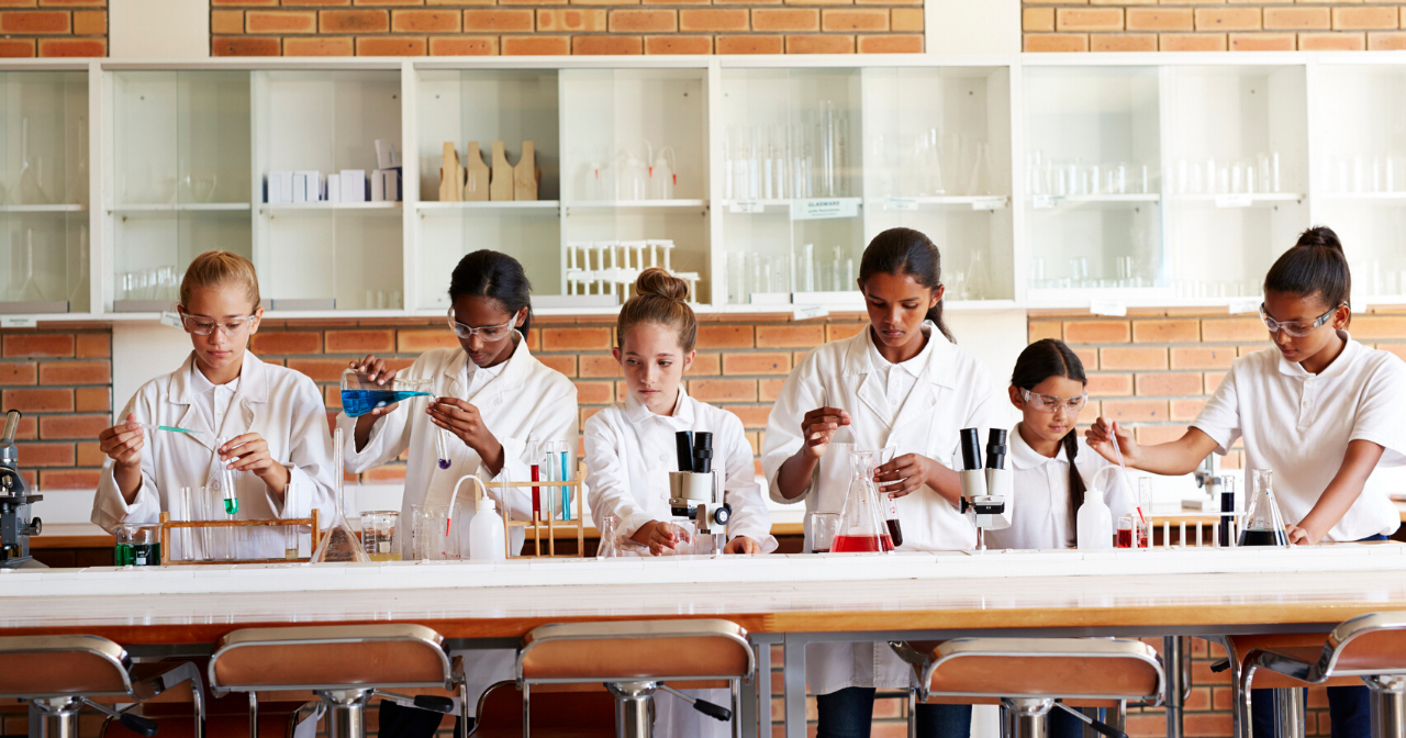 Six girls work on an experiment in a school chemistry lab