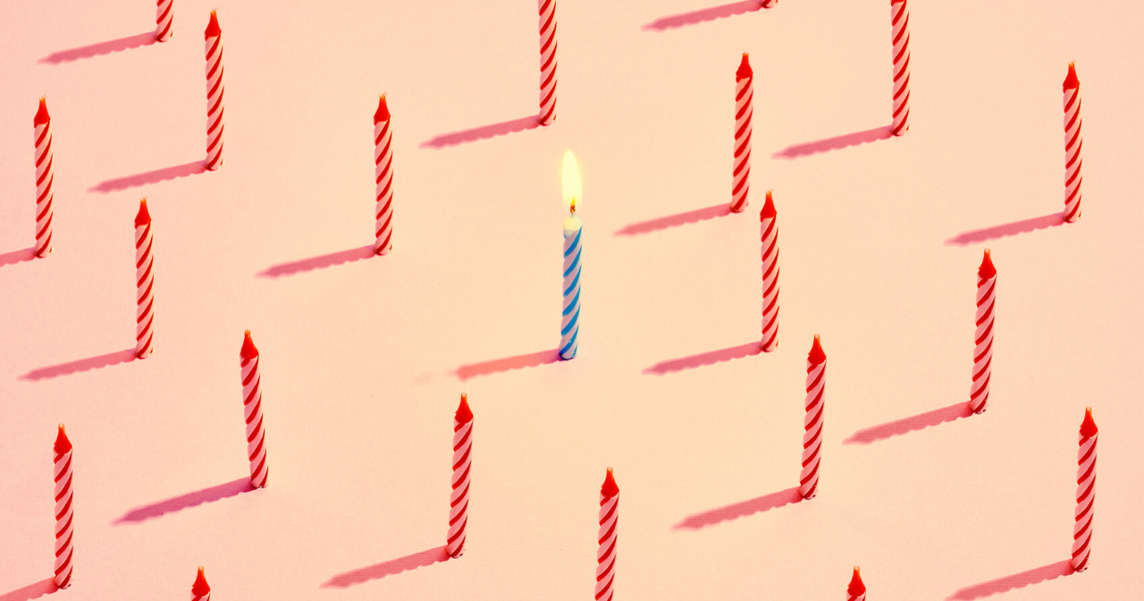 A sea of red, unlit birthday candles and one blue, lit candle in the middle.