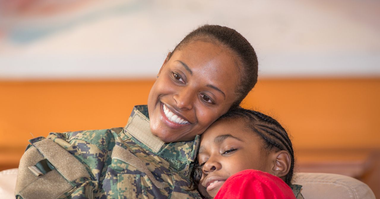 A black woman in a military uniform hugs her daughter.