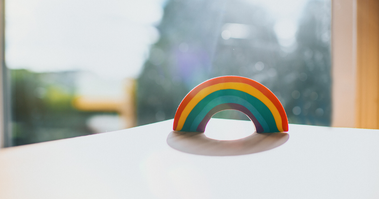 A clay rainbow sits on a tabletop in front of sunny window