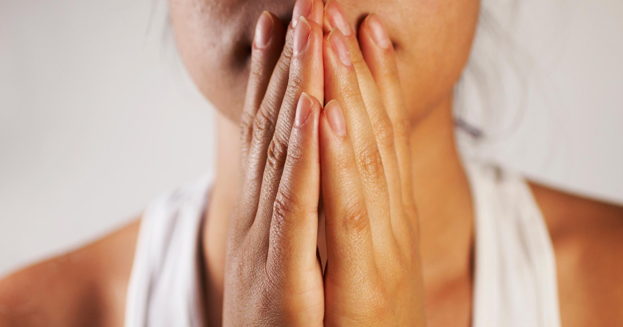 A close up of a woman's hands covering her mouth in a worried fashion.