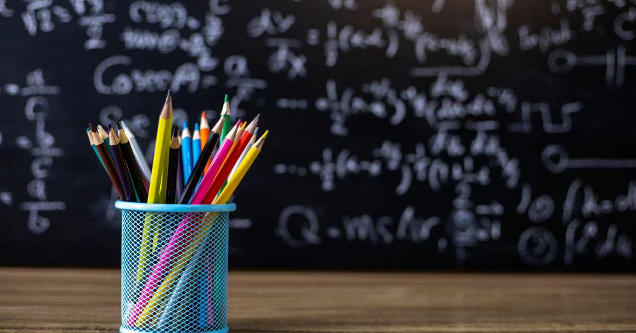 A container of colored pencils sit on a desk in front of a blackboard covered in chalk writing.