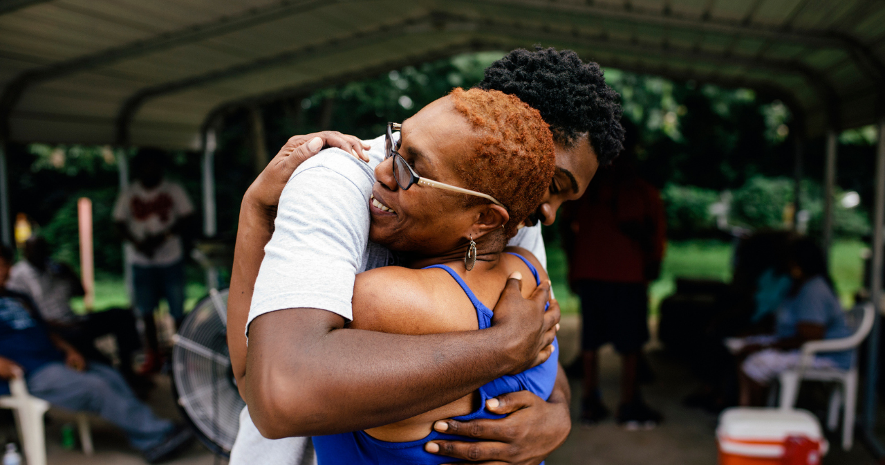 A Black woman hugs her son outdoors.