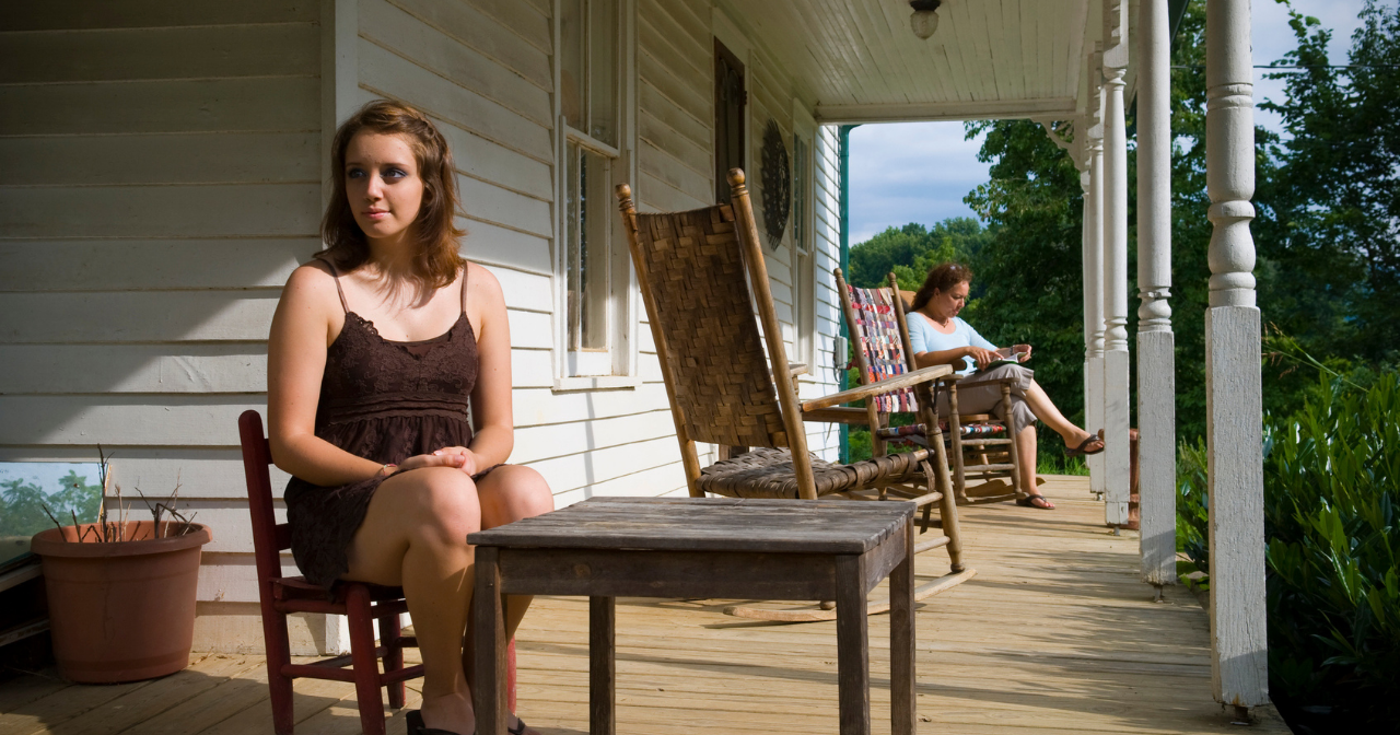 A young girl in Kentucky sits on her front porch with her mom in the background.