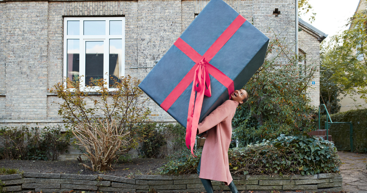 A woman walks down the street holding a comically large box.