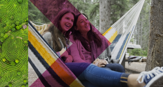 two women in a hammock, smiling