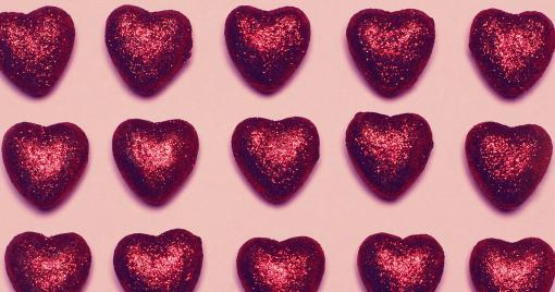 Three rows of foil wrapped hearts on a pink background.