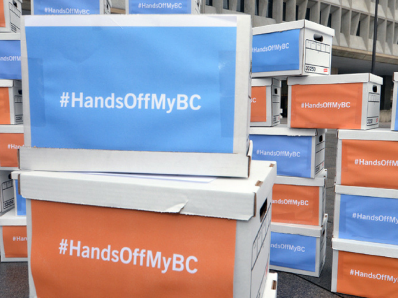 "boxes with signs that read, ""Hands Off My BC"""