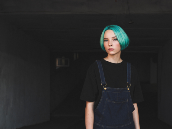 a teen with blue hair stands in an empty room