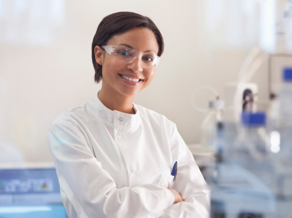 A woman in a white lab coat stands and smiles in her lab