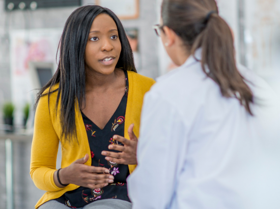 A  black woman speaks to her doctor about care