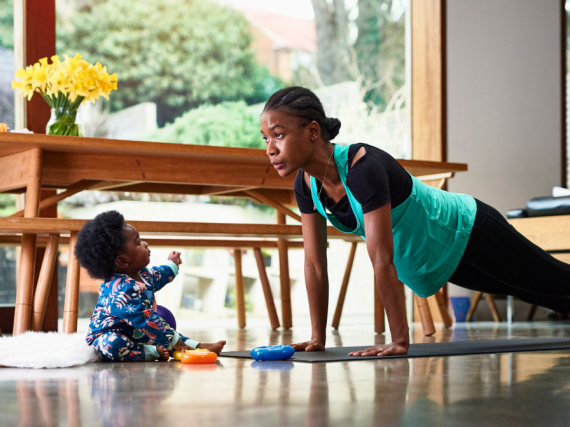 A black woman does yoga with her son watching