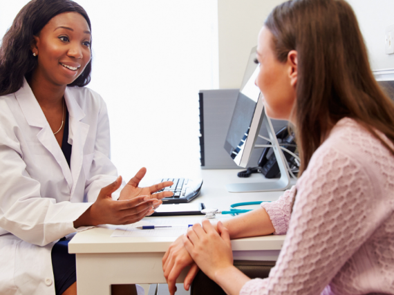 A female provider and patient talk in a doctor's office