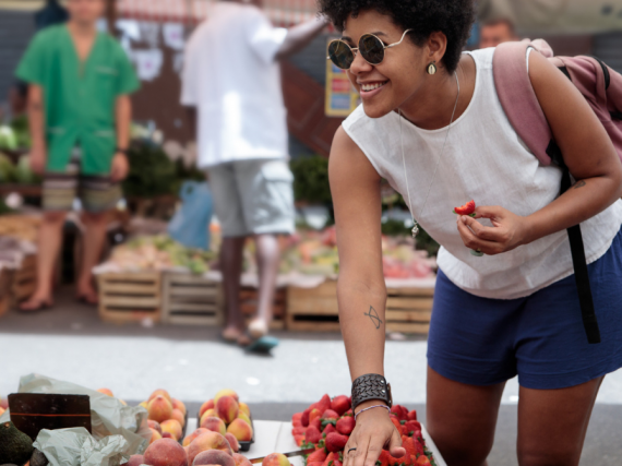 a young black woman happily looks at fruit at a farmer's market