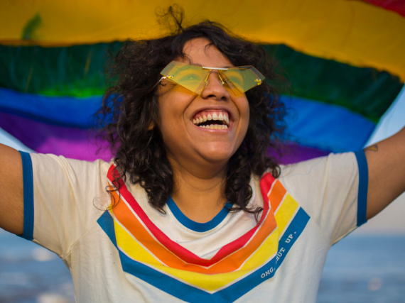A woman in a rainbow tee holds a pride flag above her head and smiles