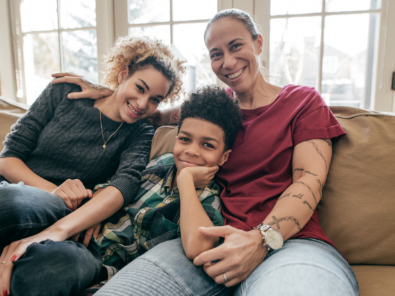 A black mother with her two children, all smiling