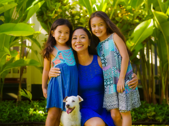 A mother, her two daughters, and a dog smile in a tropical setting.