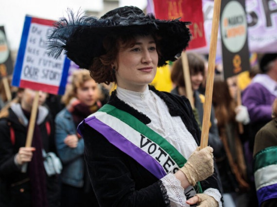 A woman dresses up as a suffragist at a modern-day protest parade.
