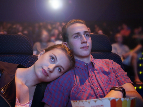 Two teens snuggle while watching a movie at the theatre.