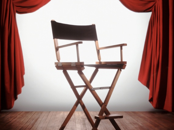 A classic director's chair sits backlit between two red velvet curtains.