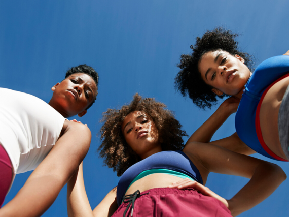 Three Black women in work out clothes stare down the camera.