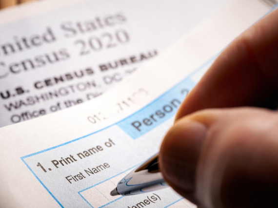 A hand holding a pen fills out the 2020 Census