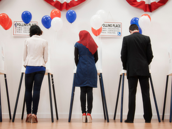 Two men and three women stand at voting booths and cast their ballots.