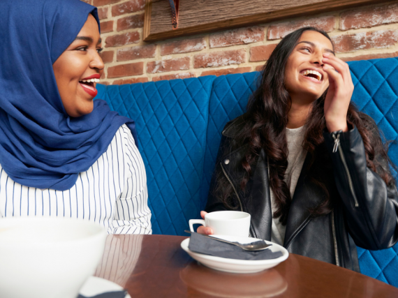 Two women sit at a table in a cafe and laugh over cups of coffee.