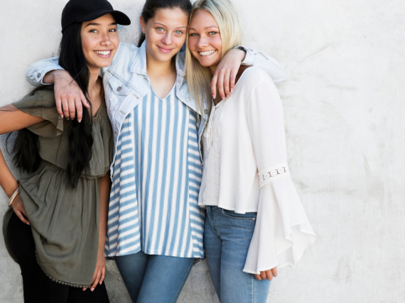 Three young women pose for a picture with their arms around each other and big smiles.