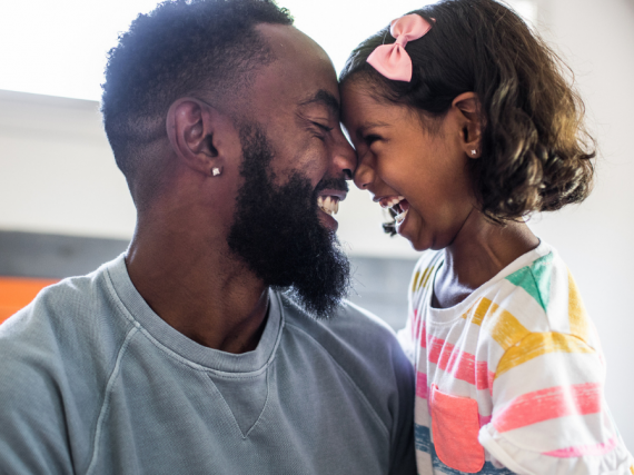 A Black father and his young daughter smile and hug.