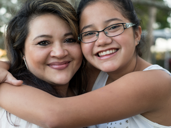 A Latina mom and her daughter hug and smile at the camera.