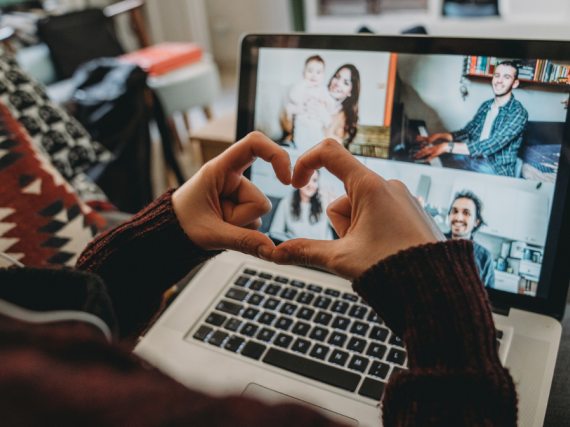 A person makes a heart with their fingers in front of their computer during a Zoom call with friends.