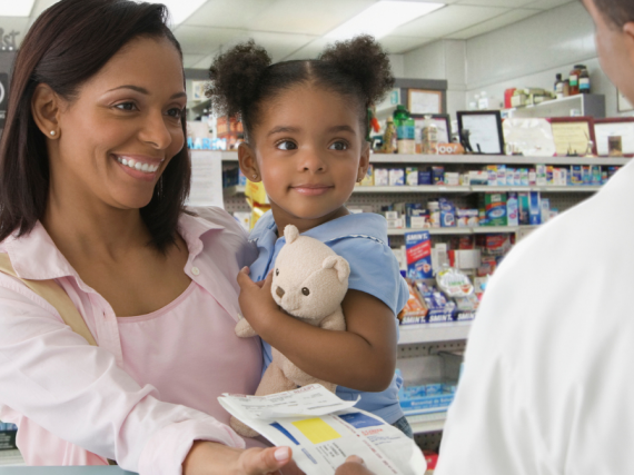 A mother and her young daughter pick up a prescription at the pharmacy.