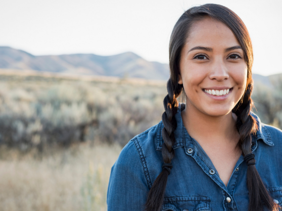 A young Native woman smiles for the camera while standing among a field of wild grasses.