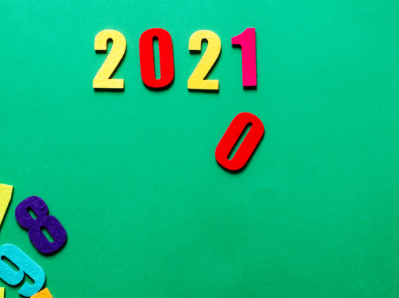 Refrigerator magnets in the shape of numbers sit on a green background. 2021 is spelled out with a zero falling down under where the 1 sits.