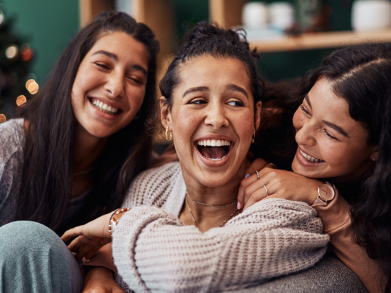 Three sisters laugh in their living room.