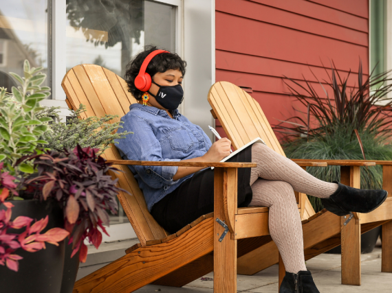 A Latinx person sits in a chair outside while wearing a facemask and writing a letter.