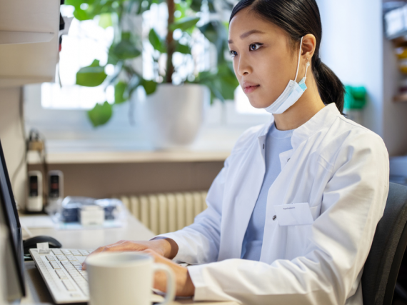 A pharmacist sits alone at a computer with their mask sitting below their face as they work on prescriptions.
