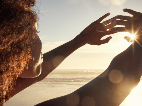A Black woman stands on the beach and holds her hands up so she can look at the sunset.